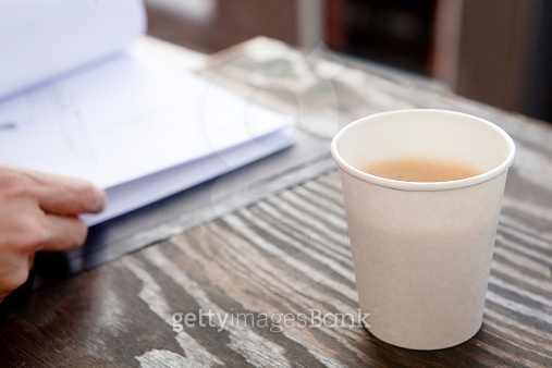 Young woman at work drinking coffee from disposable cup.