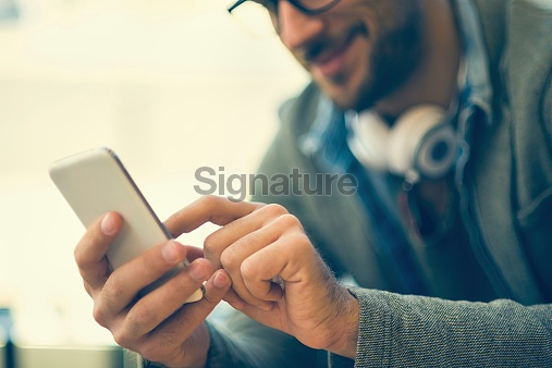 smiling man typing text message