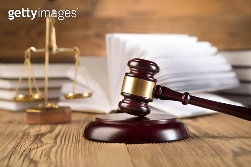 Golden scales of justice, gavel and books wood brown background