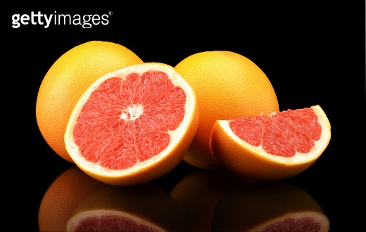 Studio shot sliced three grapefruits isolated black