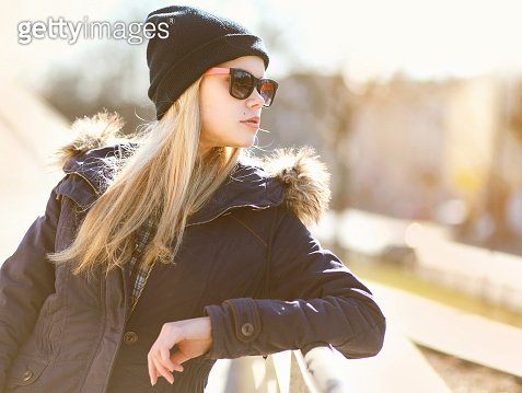 Portrait fashion hipster girl in the city in sunny day