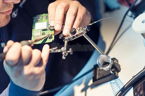 Technician Worker Soldering Elements on Microchip Circuit Board