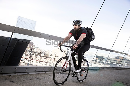 Commuter cycling fast at work in the morning
