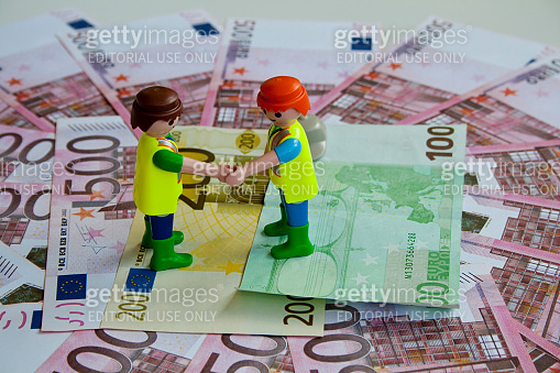 Two toy workers shake his hands to reach money agreement.