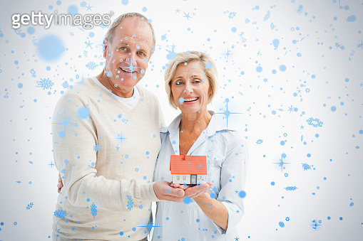 Happy mature couple with model house