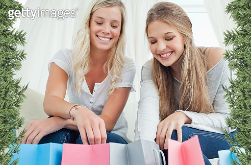Smiling girls looking into the bags below them