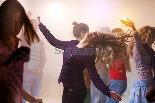 Group of young happy people dancing at nightclub.