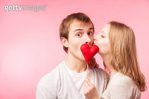 Girl kissing boy hiding behind a little red heart