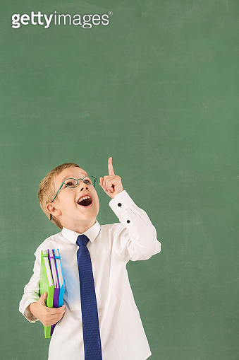 Schoolboy pointing at copy space on the blackboard