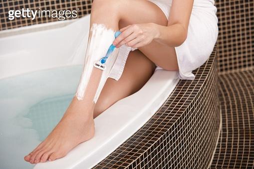 Long Woman Legs . Woman Shaving Legs in Bathroom