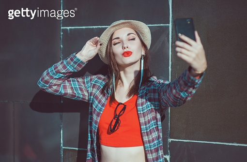 Young hipster girl in the hat taking picture of herself