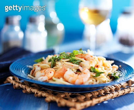 white wine and shrimp pasta with basil on blue plate