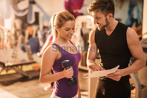 Smiling coach and young woman making a workout plan together.