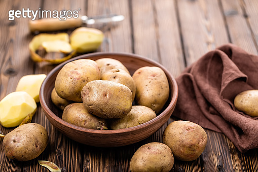 raw potato on wooden table top view