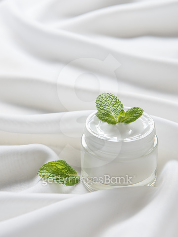 The moisturizing cream with green  leaves on the white silk