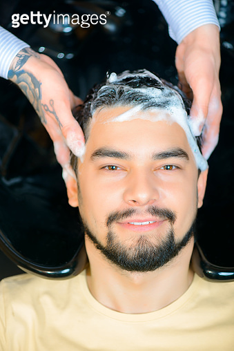 Professional barber washing hair of the client