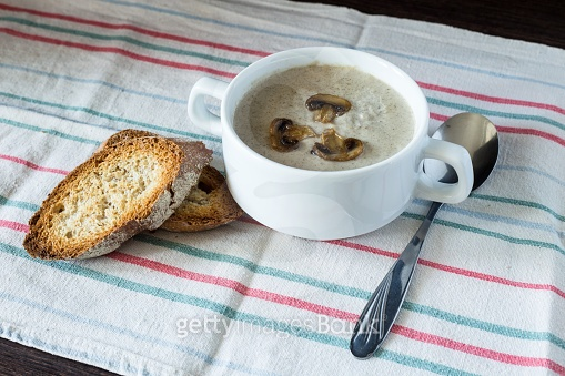 Bowl of mushroom soup with bread on wooden board