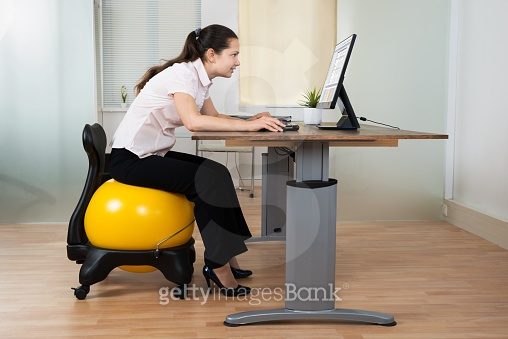 Businesswoman Bending While Sitting On Fitness Ball