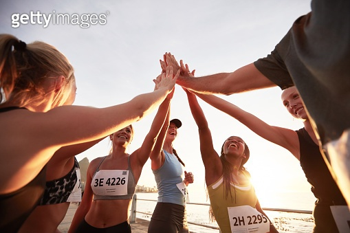 Group of athletes high fiving after race