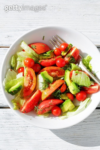 summer salad in bowl on sunlight