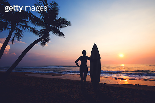 Silhouette women surfer on tropical beach