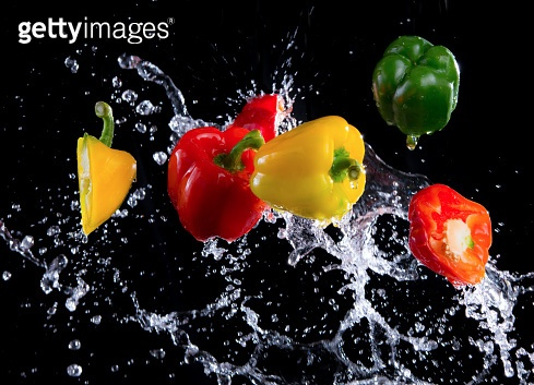 Bell peppers with splash isolated on black background, motion action.