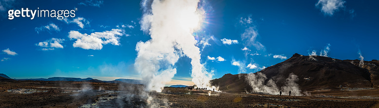 Volcanic steam from geysers rising above incredible landscape panorama Iceland