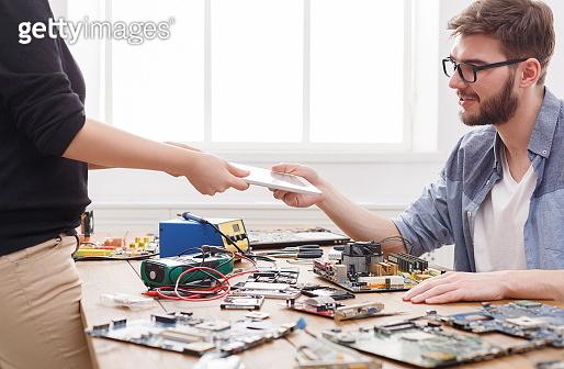Engineer taking broken tablet from client