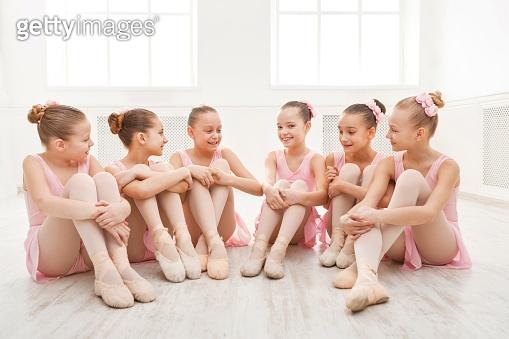 Little ballerinas talking in ballet studio