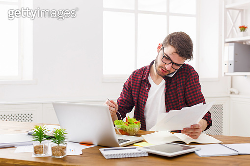 Busy man has business lunch in modern office interior