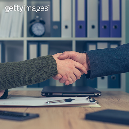 Man and woman shake hands over business agreement