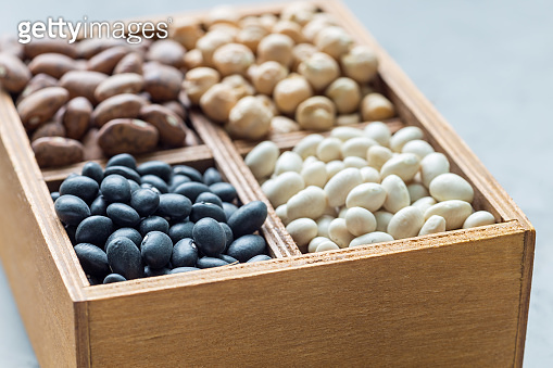 Different kinds of beans: black, pinto, white and chickpeas in wooden box on concrete background, horizontal
