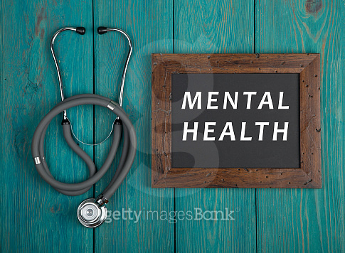 Blackboard with text 'Mental health' and stethoscope on blue wooden background