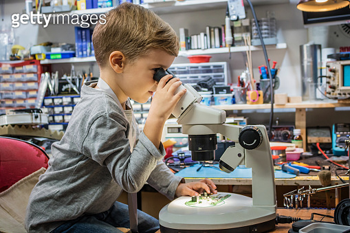 Small boy examining chip on mother board under the microscope.