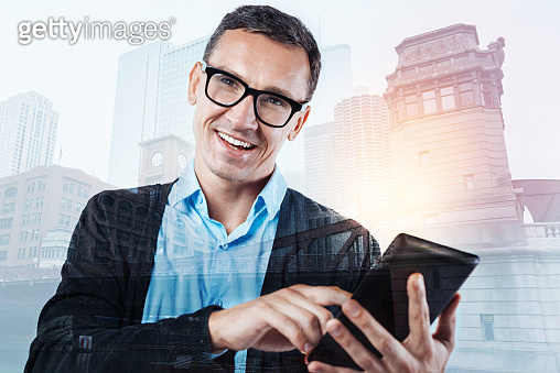 Joyful cheerful man using his electronic device