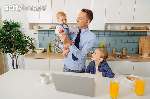Happy delighted man standing in the kitchen with his daughter