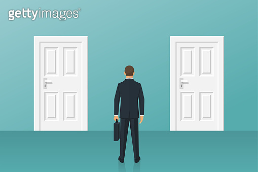Businessman standing in front of two closed doors.
