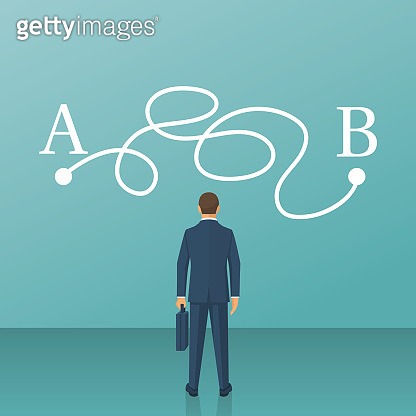 Businessman in suit standing in front of tangled paths.