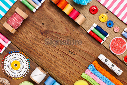 Overhead flat lay of sewing items arranged on wood