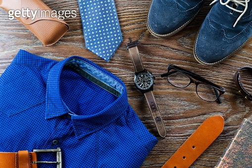 Stylish man clothing and accessories flat lay in blue and brown colors on a wooden background