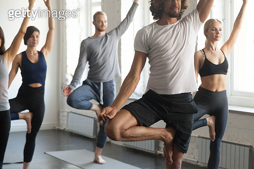 Group of young sporty people in Tree pose, studio