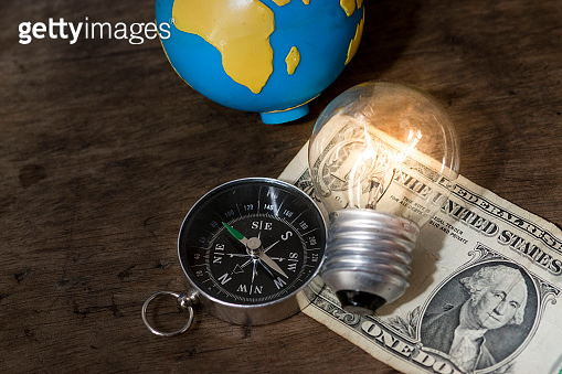 Navigation compass on top of a dollar bill, and a wooden