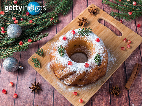 Christmas cake in the shape of a wreath with Christmas decorations. Pomegranate anise star fir-tree branches.