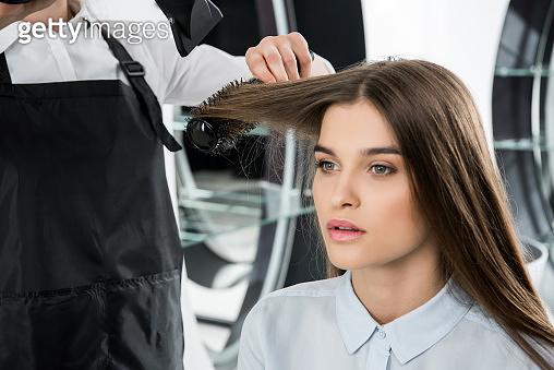hairdresser brushing hair of woman
