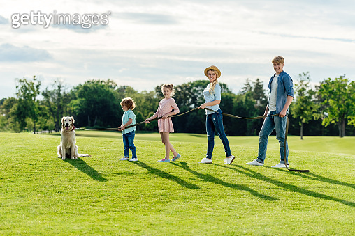 side view of happy young family with pet walking on green meadow at park