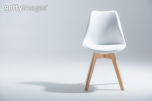 stylish chair with white top and light wooden legs standing on white