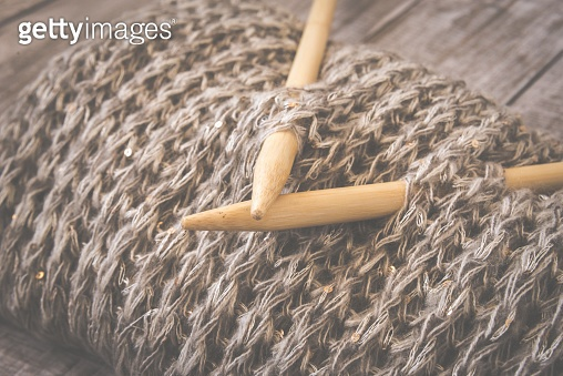 Detail of woven handicraft knit woolen design texture and knitting bamboo needle. Toned retro. Rustic wooden background.
