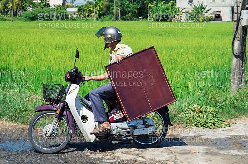 Vietnamese man transporting a table on a motorscooter