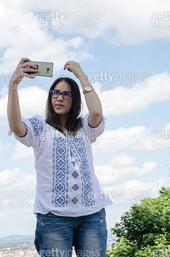 Beautiful young woman arring her hair before taking a selfie outside