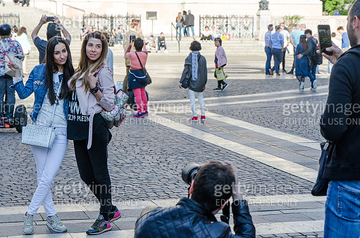 Two young women being taken in picture by a friend in front of Budapest Basilica